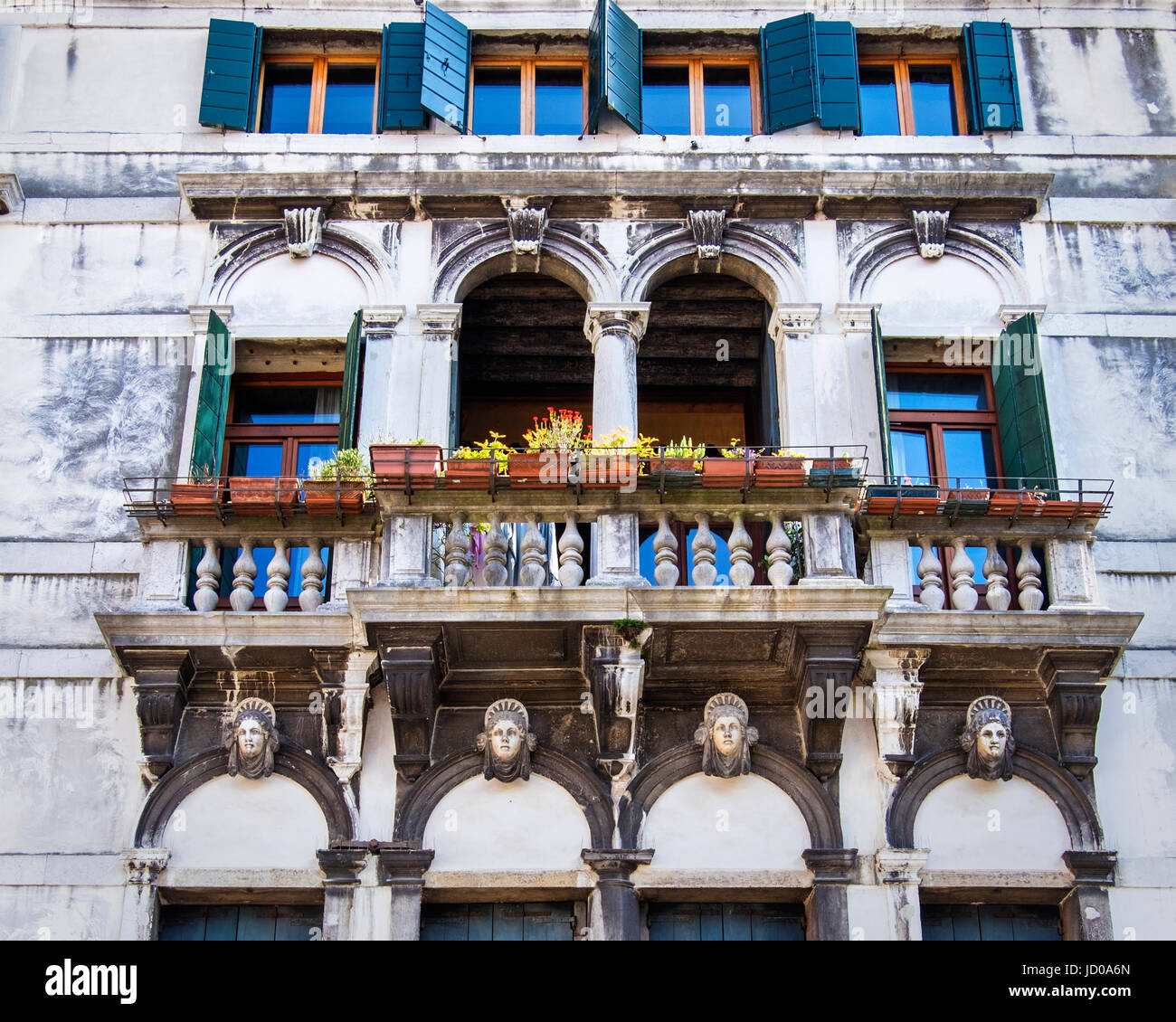 Venice Italy.Venetian weathered building exterior facade with elegant arched windows,balcony,pot plants and sculptural - Stock Image