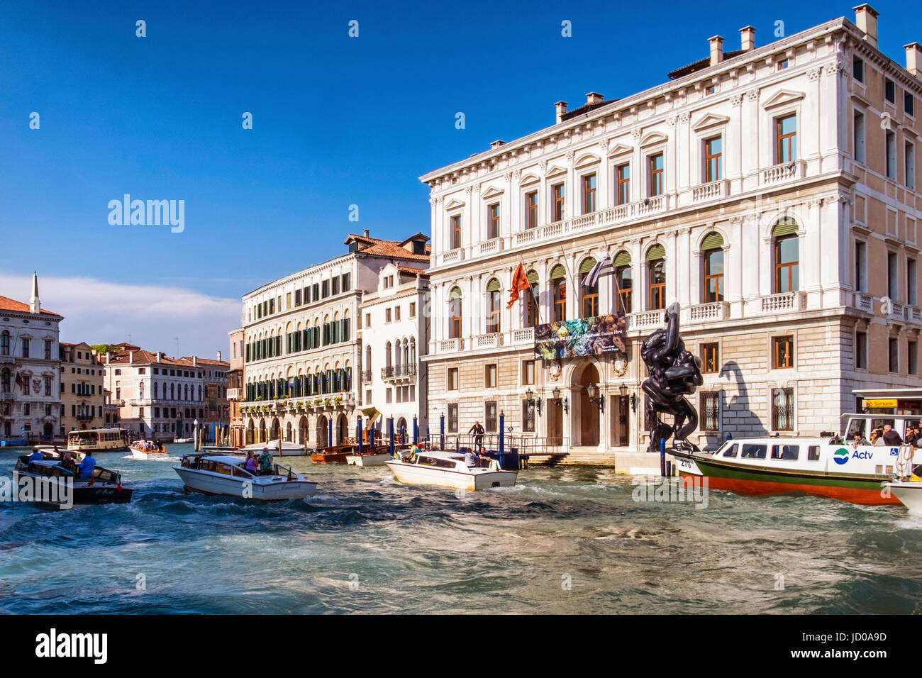 Venice,Italy. Water taxis race past the Palazzo Grassi Palace on the Grand canal shows British artist,Damien Hirst - Stock Image