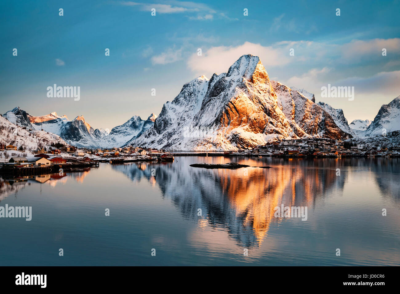 Mount Olstind reflected in the calm waters of Reinfjord on the Lofoten Islands Stock Photo