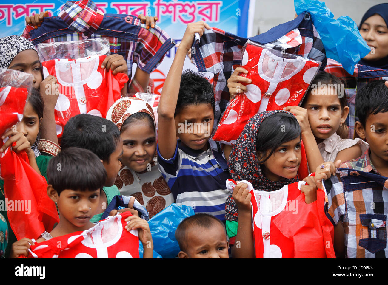 Bangladeshi street children hold their new cloth after zakat distribution by social activist in Dhaka for celebrate - Stock Image