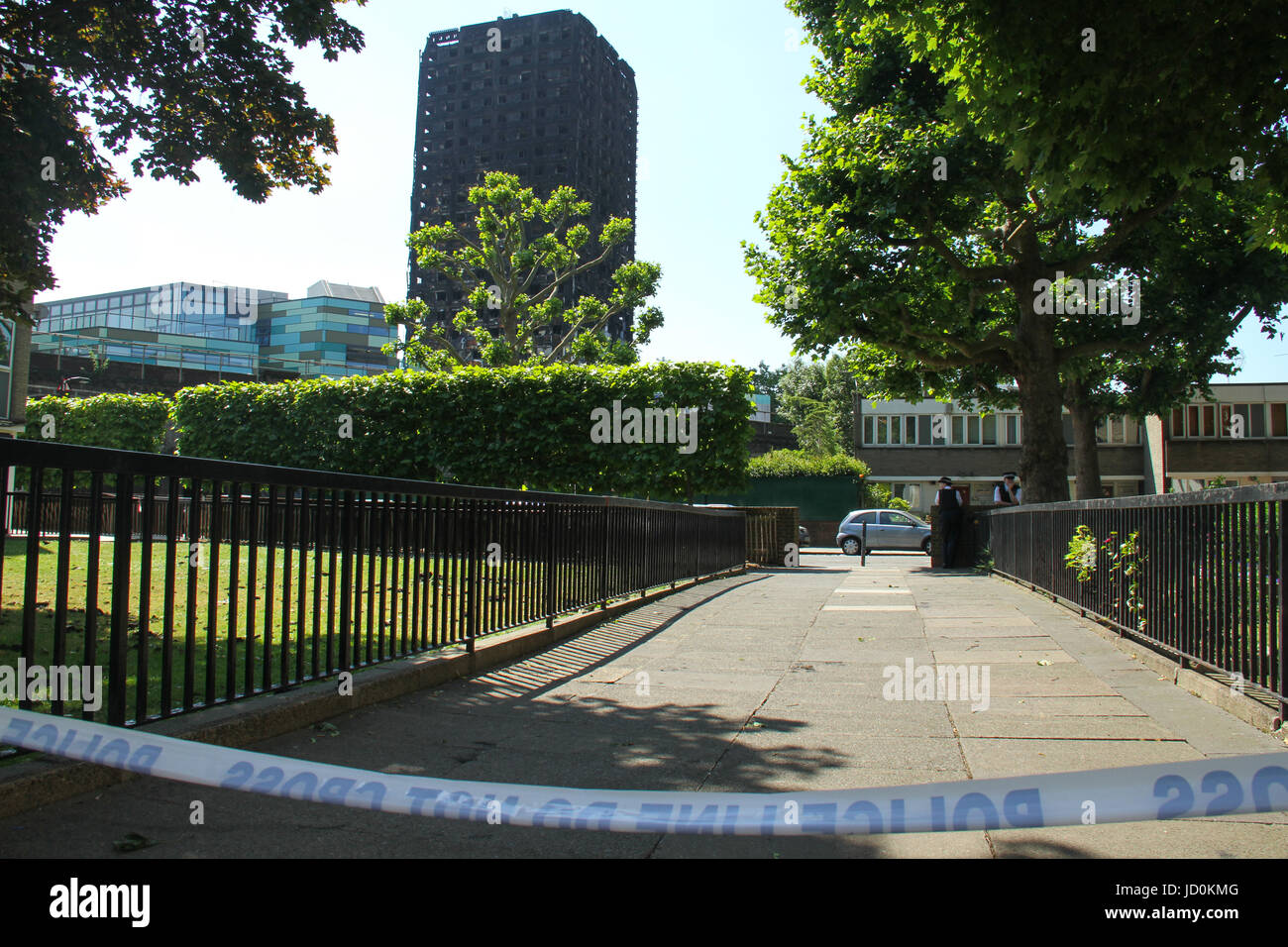 London, UK. 16th June, 2017. Police offices stand on guard along a cordoned area around the charred remains of the - Stock Image