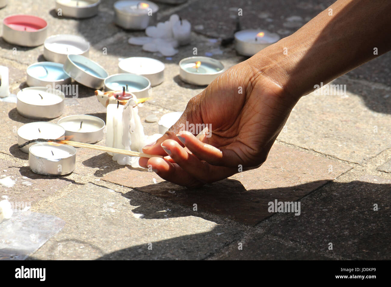 London, UK. 16th June 2017. A woman lights up a candle outside the Notting Hill Methodist Church for the Grenfell - Stock Image