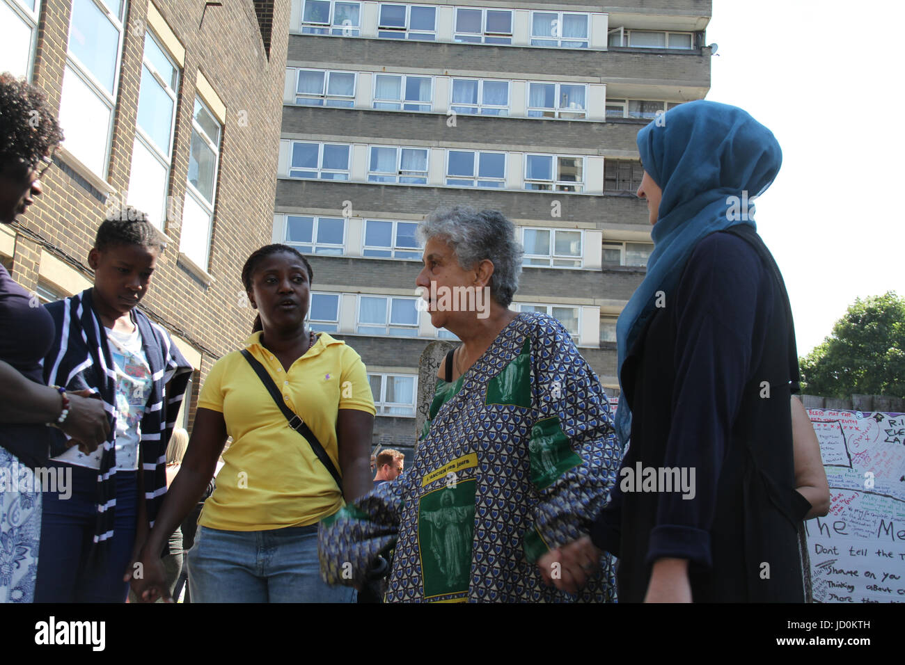 London, UK. 16th June 2017. A group of women join hand in song by a Grenfell Memorial wall. At least 30 people have - Stock Image