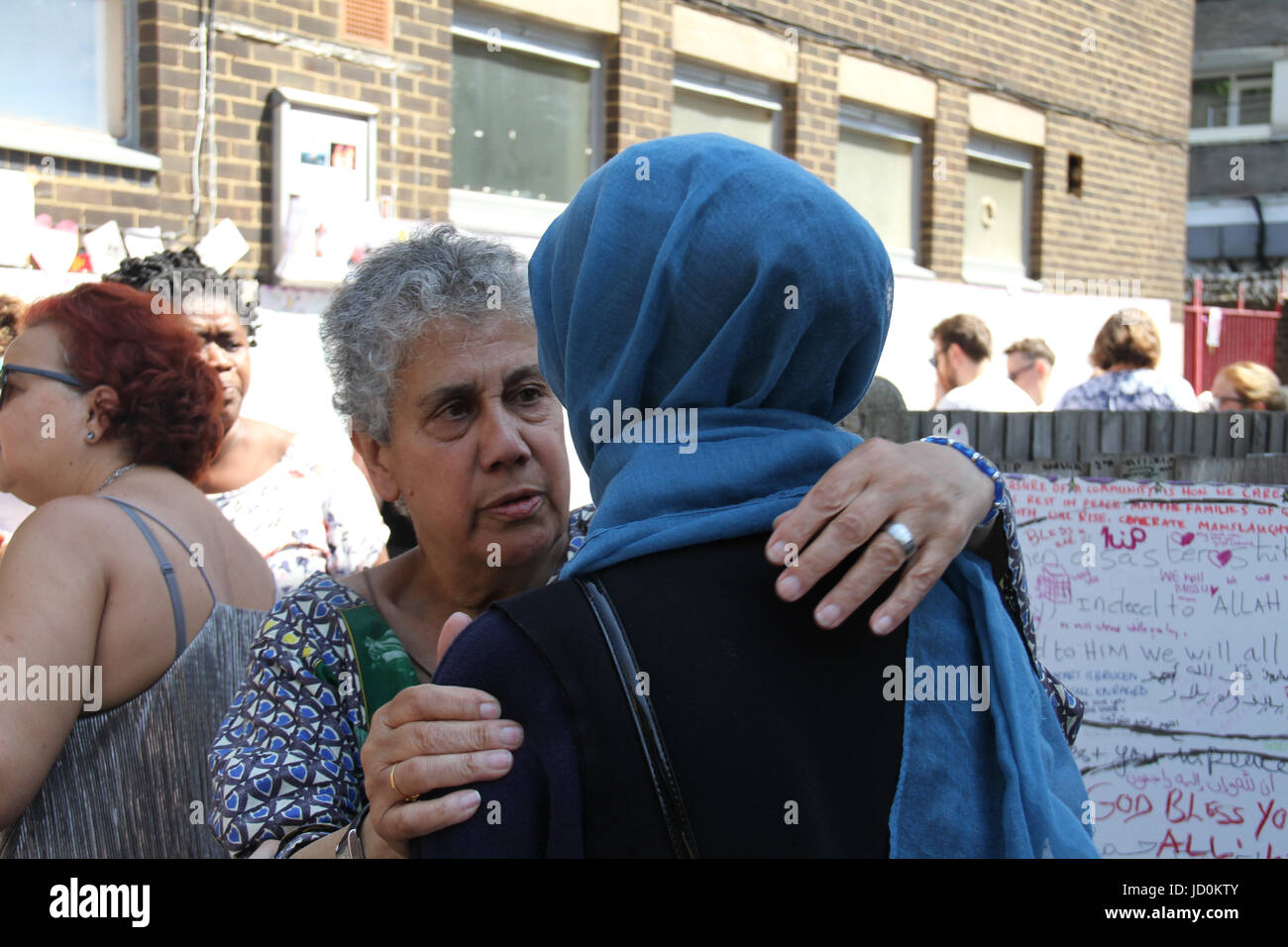 London, UK. 16th June 2017. A Muslim woman is welcomed to sing along by a Grenfell Tower memorial on 17 June. At - Stock Image