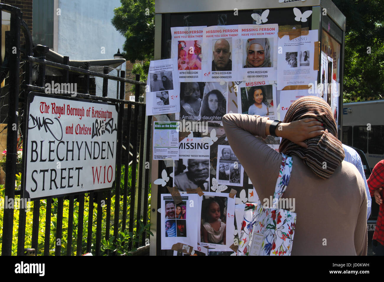 London, UK. 16th June 2017 - A woman reads through missing person posters on Blechynden Street following the Grenfell - Stock Image