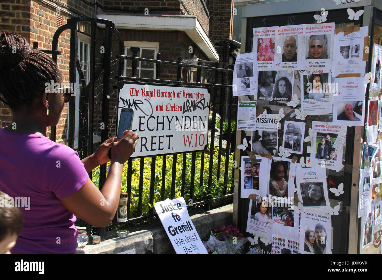 London, UK. 16th June 2017 - A woman takes photos of Missing person posters stuck on a phone booth on Blechynden - Stock Image