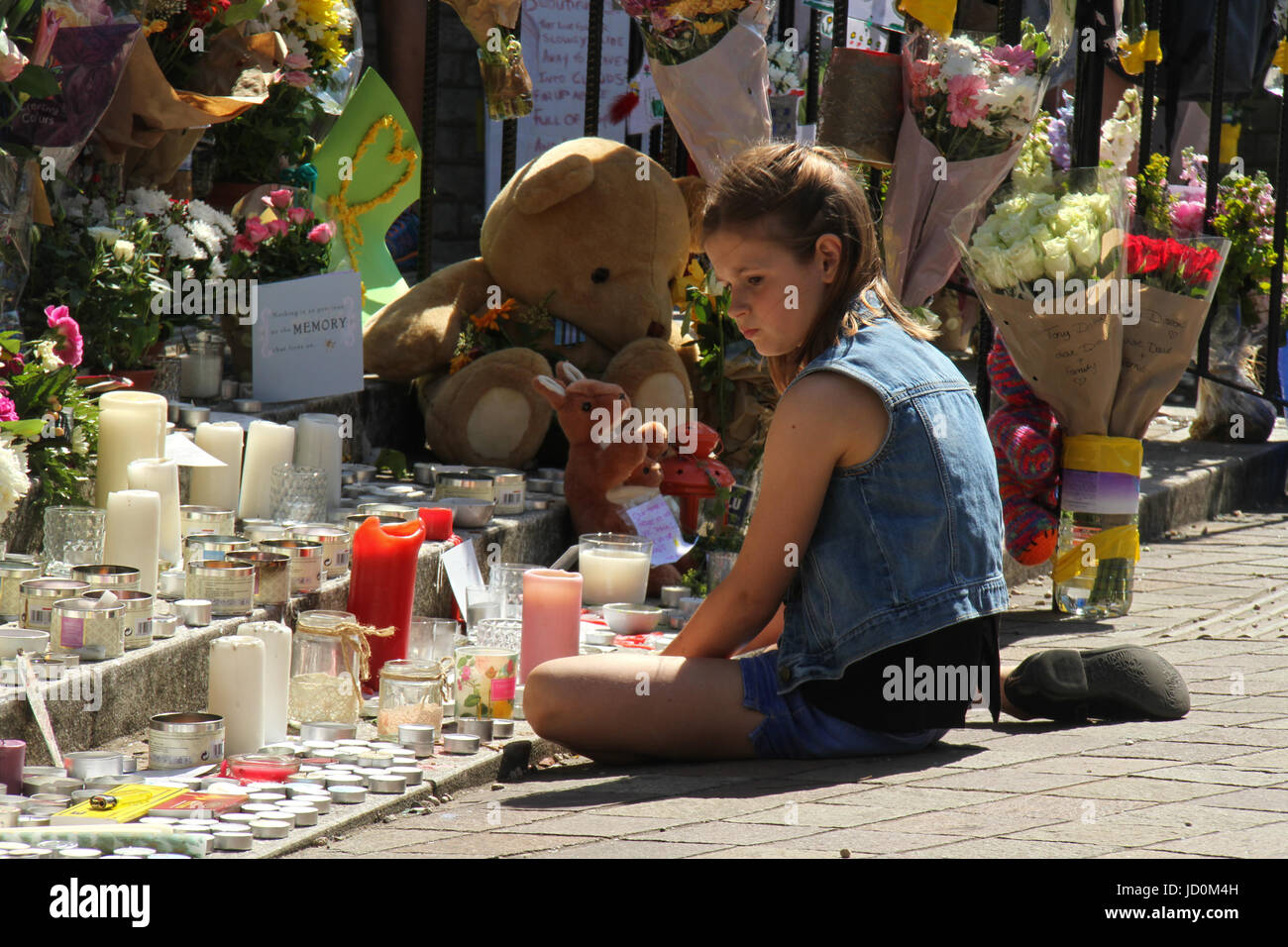 London, UK. 16th June, 2017. A young girl is seen sitting by the Grenfell Memorial outside the Notting Hill Methodist - Stock Image