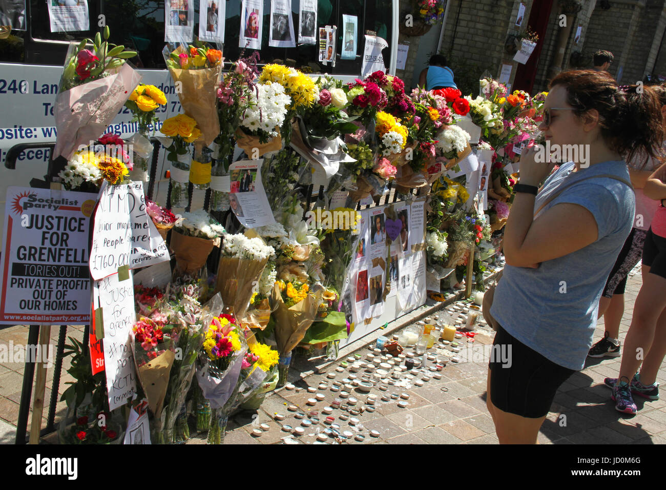 London, UK. 16th June, 2017. A woman seen reading through memorial messages places outside the Notting Hill Methodist - Stock Image