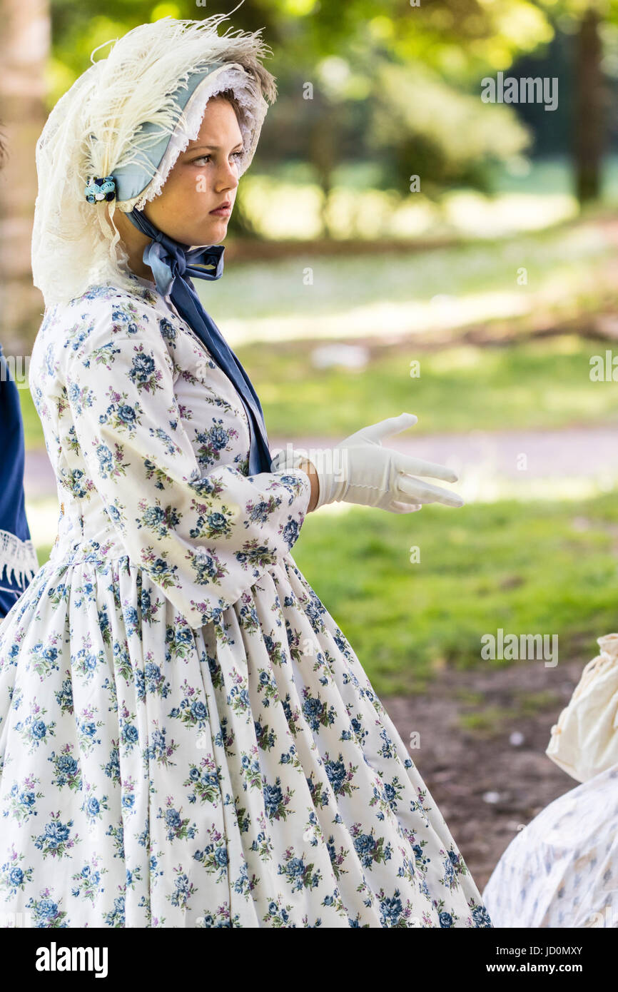 Pretty young teenage, 14-15, woman standing in park dressed up in Victorian costume. White dress with blue flowers Stock Photo