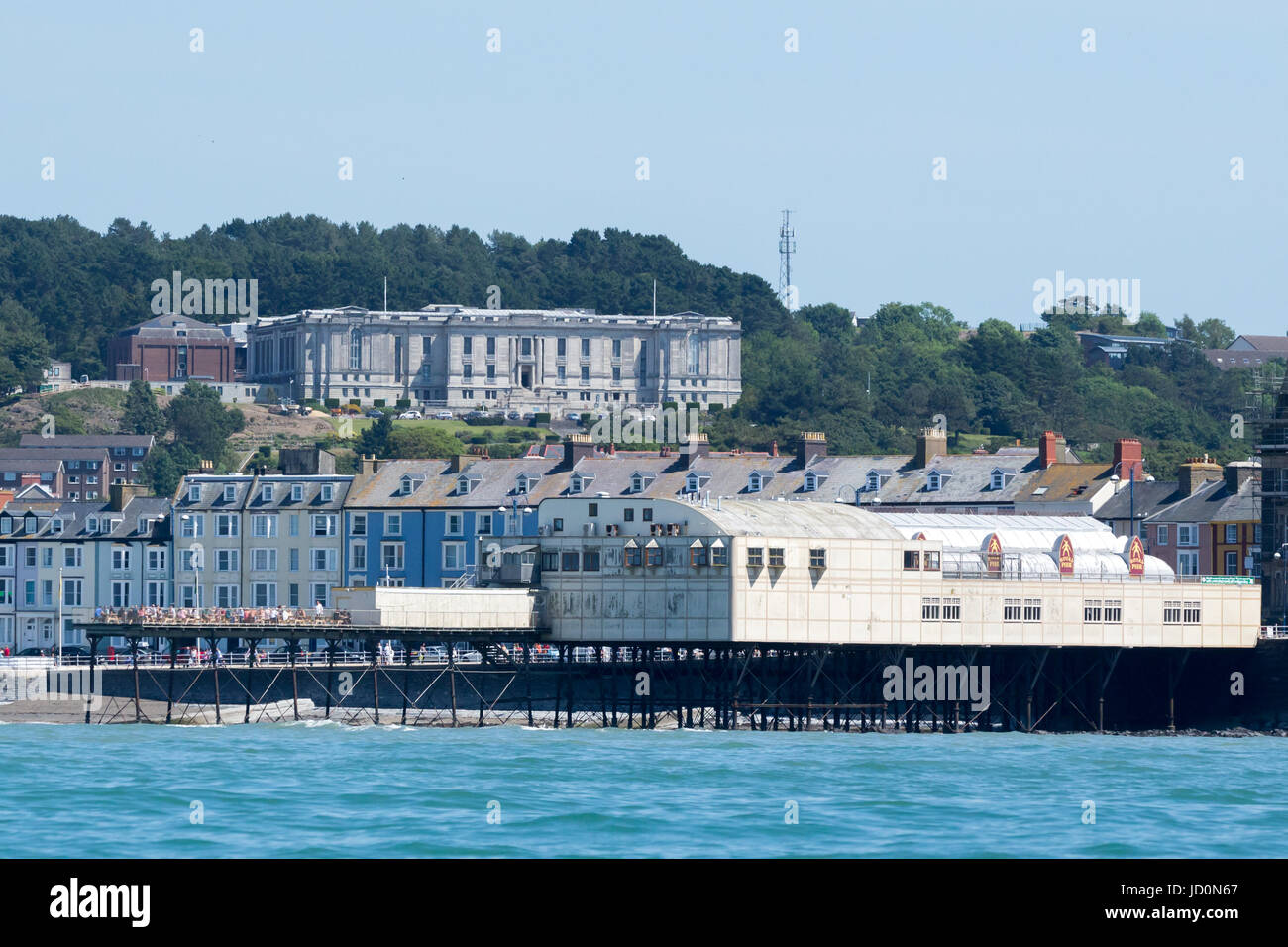 A view of Aberystwyth seafront pier with the National library of Wales in the background - Stock Image
