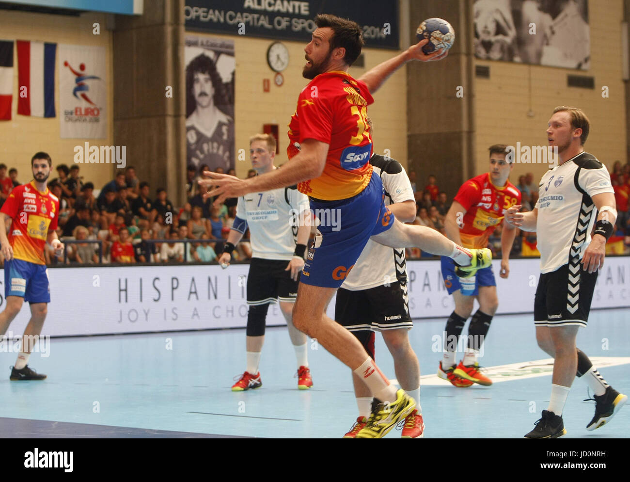 Spanish handball national team's player Gideon Guardiola (C) shoots the ball as Finnish Koljonen (R) looks on - Stock Image