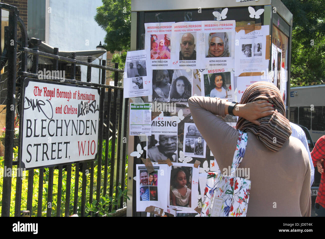 London, UK. 17th June 2017 - A woman reads through missing person posters on Blechynden Street following the Grenfell - Stock Image