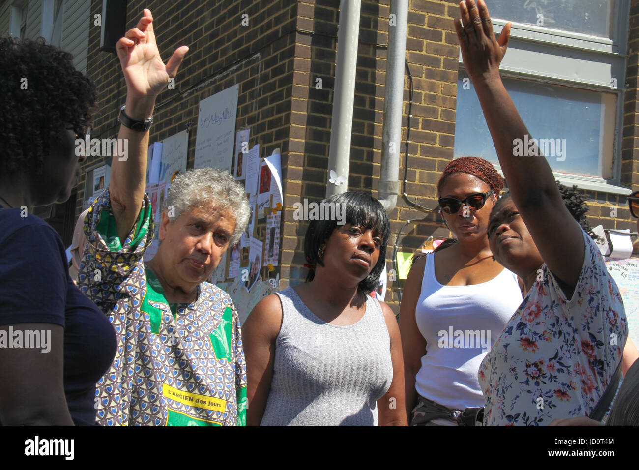 London, UK. 17th June 2017 - A group of women join hand in song by a Grenfell Memorial wall. At least 30 people - Stock Image