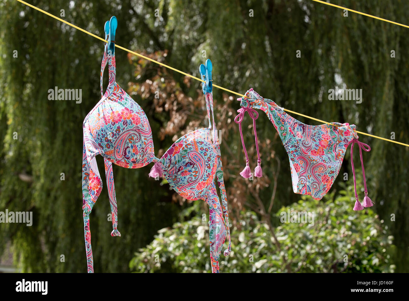 A colorful bikini hanging on a washing line - Stock Image