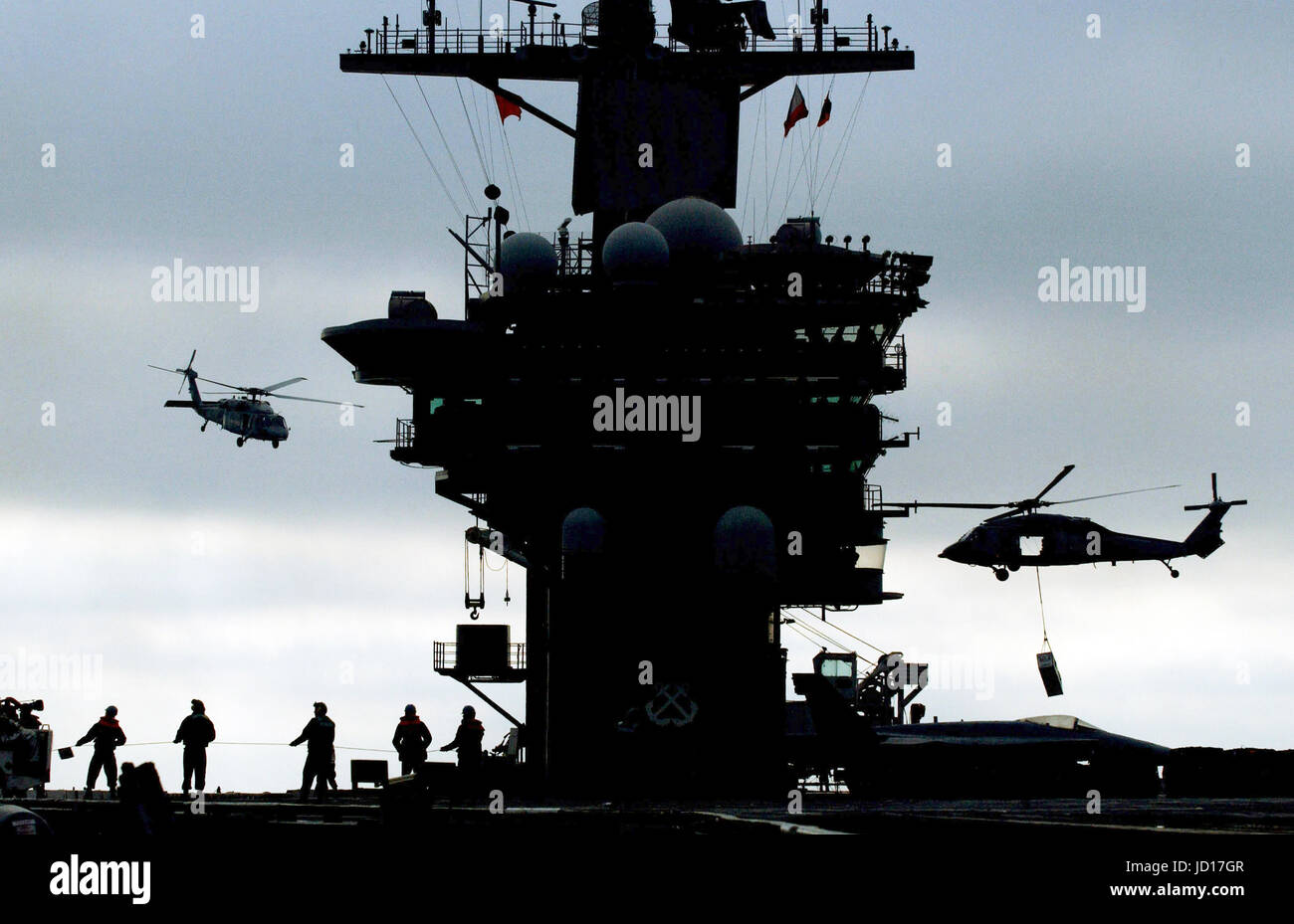 Navy MH-60S Seahawk helicopters airlift ammunition from the aircraft carrier USS Nimitz (CVN 68) to the Military - Stock Image