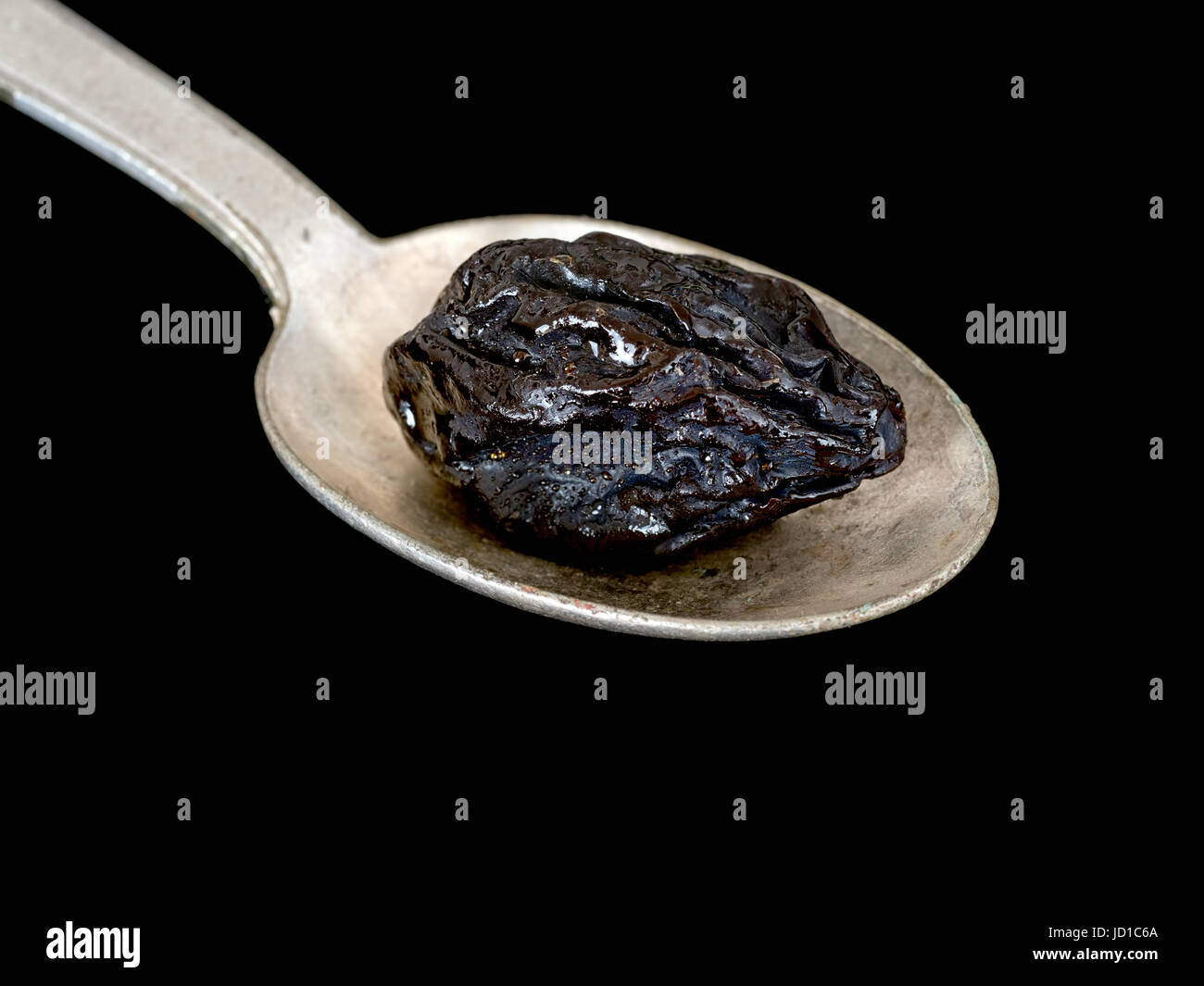 Prune on spoon. High in iron, boron and a traditional, natural remedy for constipation as a natural laxative. - Stock Image