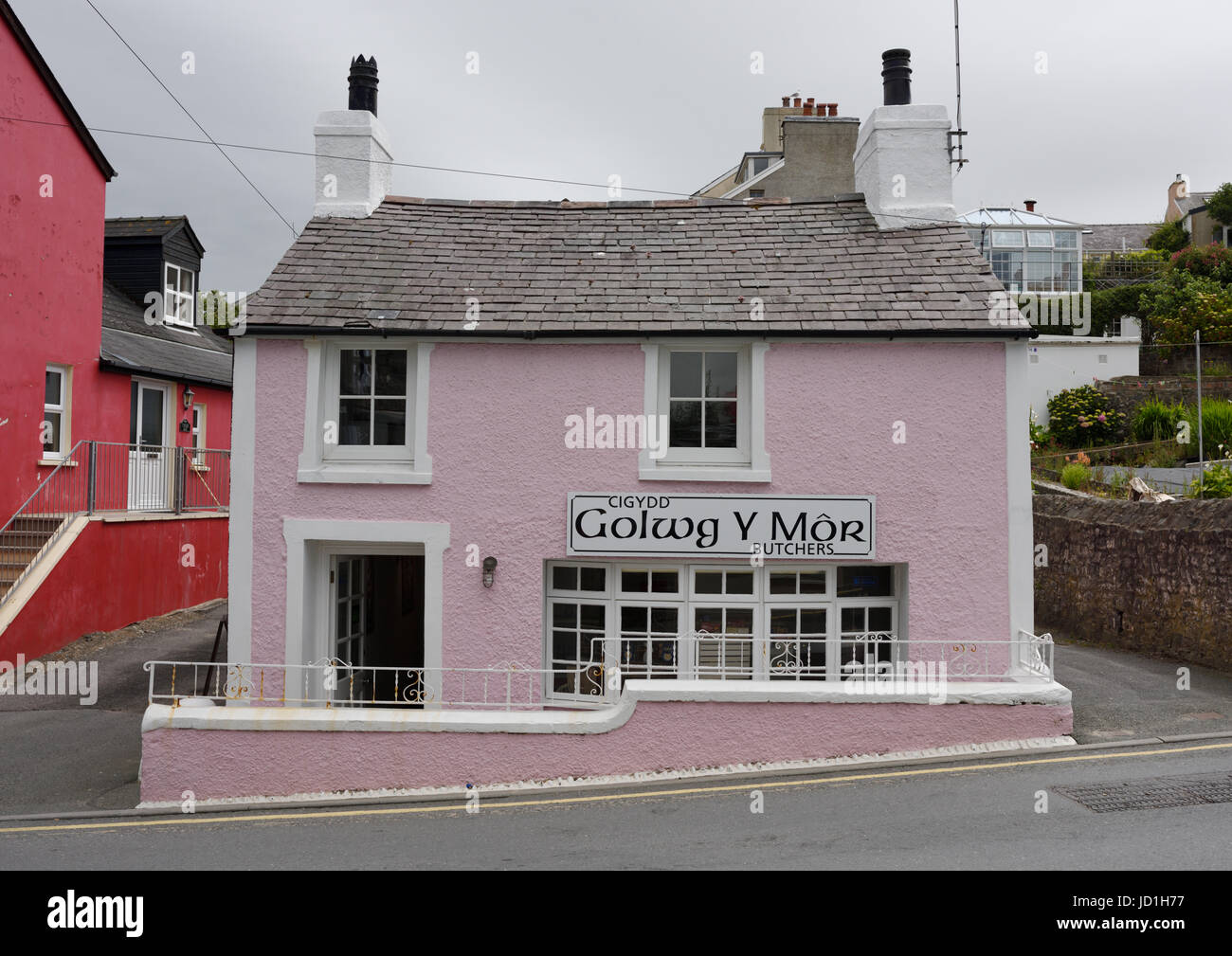 Pink painted butcher shop with slate roof, built on slope in west wales - Stock Image