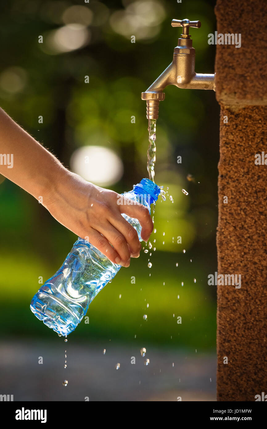 Close up of female hand pouring water in plastic bottle on faucet outdoors. Nature, summer and healthy lifestyle - Stock Image