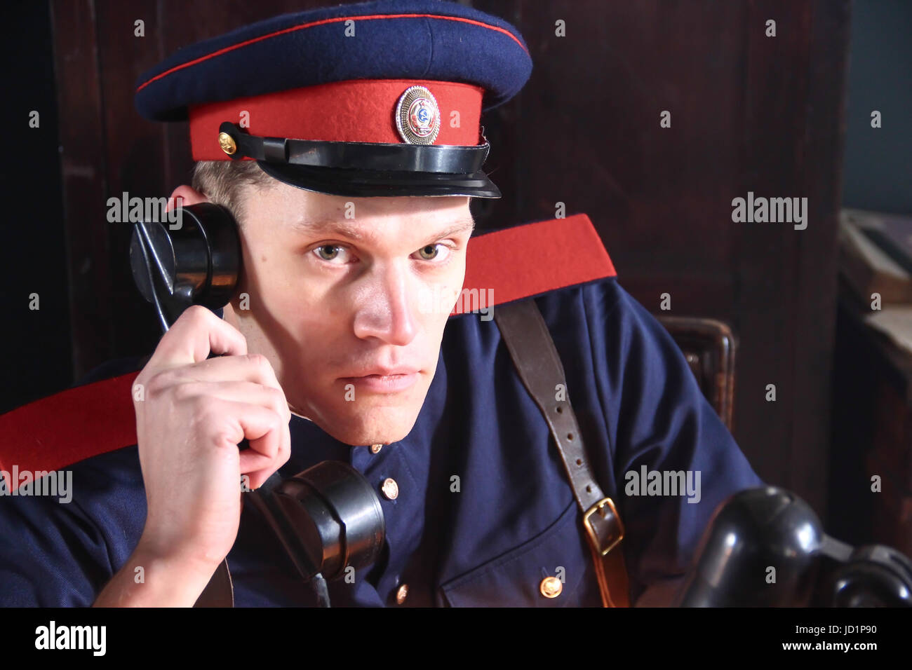 Soviet police officer (militiaman) 50s of 20th century, talking on the phone in the service area (modern reconstruction) - Stock Image
