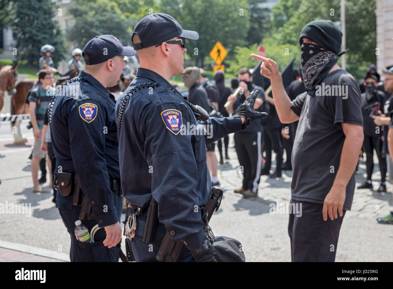 Harrisburg, Pennsylvania - A Black Bloc anarchist argues with police during the Bloc's counter-demonstration - Stock Image