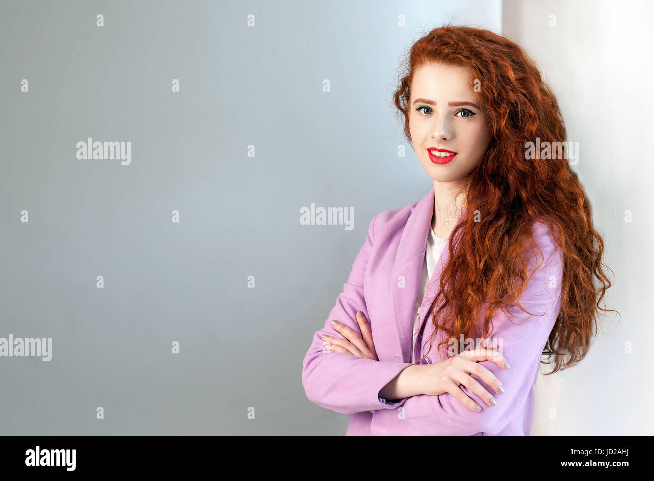 Portrait of successful happy beautiful business woman with red - brown hair and makeup in pink suit. looking at Stock Photo