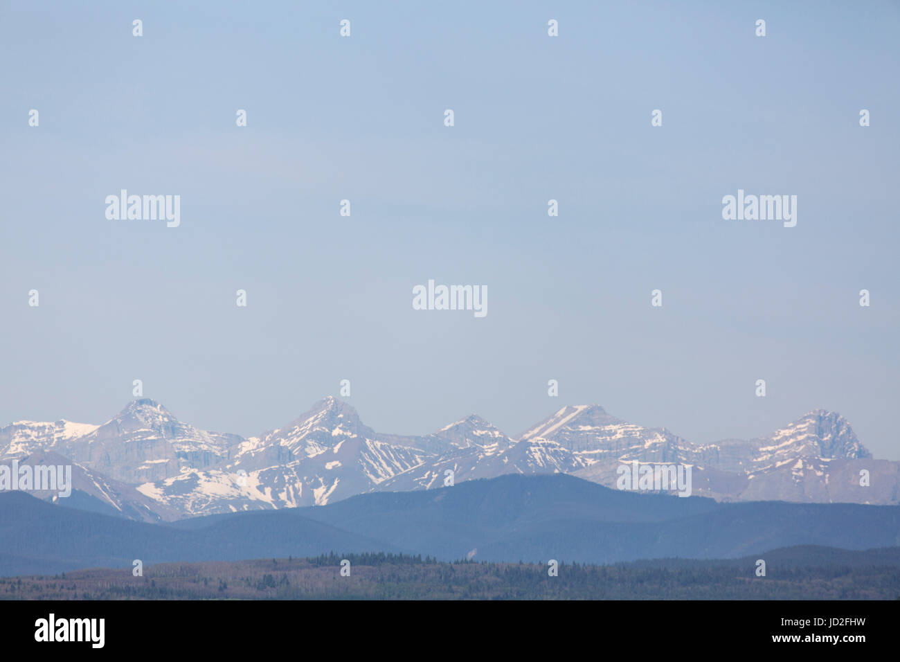 Snow-capped peaks in the Canadian Rockies at Banff National Park in Alberta, Canada. The snow can be seen into summer. - Stock Image