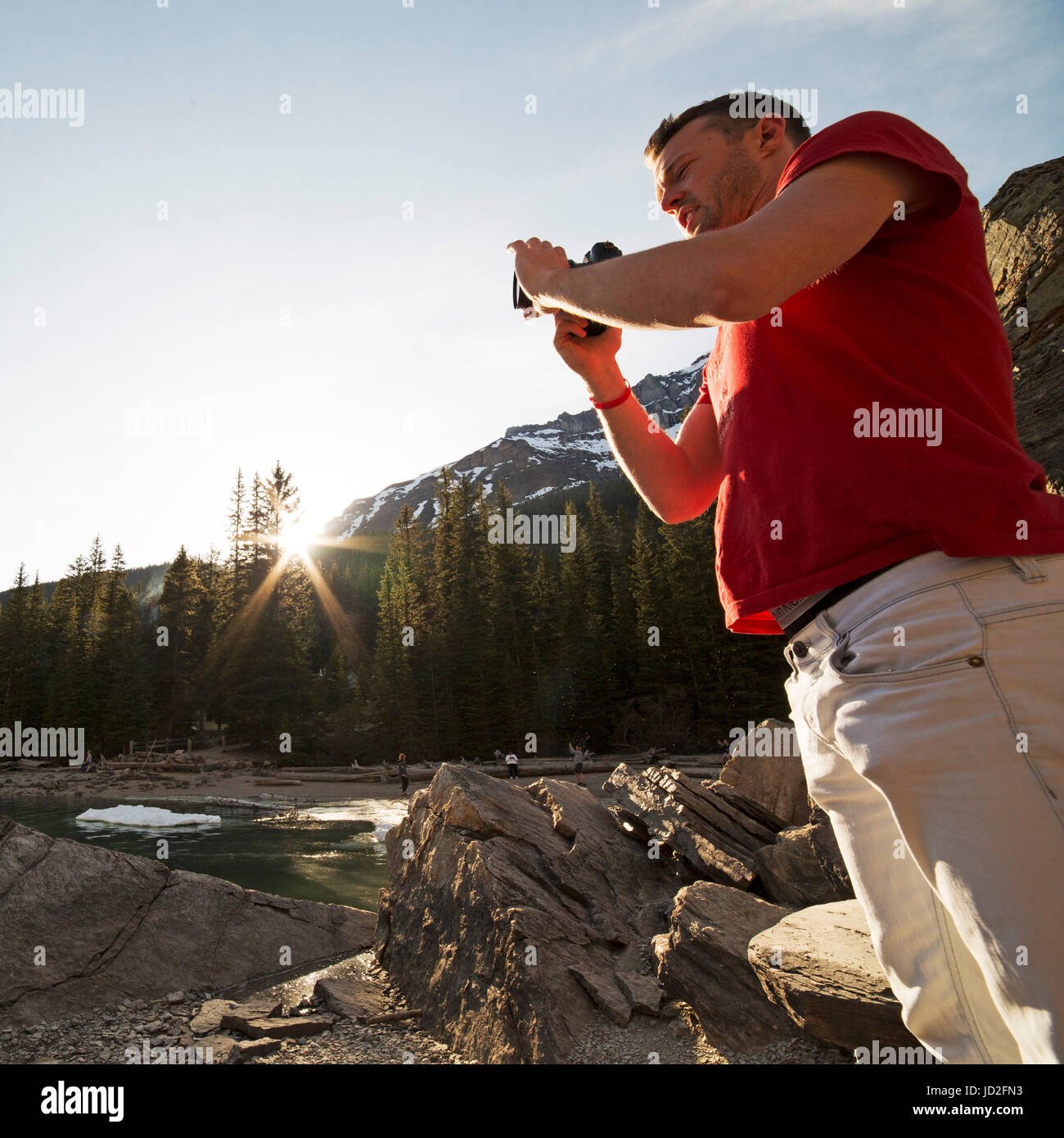 A man photographs as sun bursts above the forest by Moraine Lake in the Canadian Rockies at Banff National Park - Stock Image