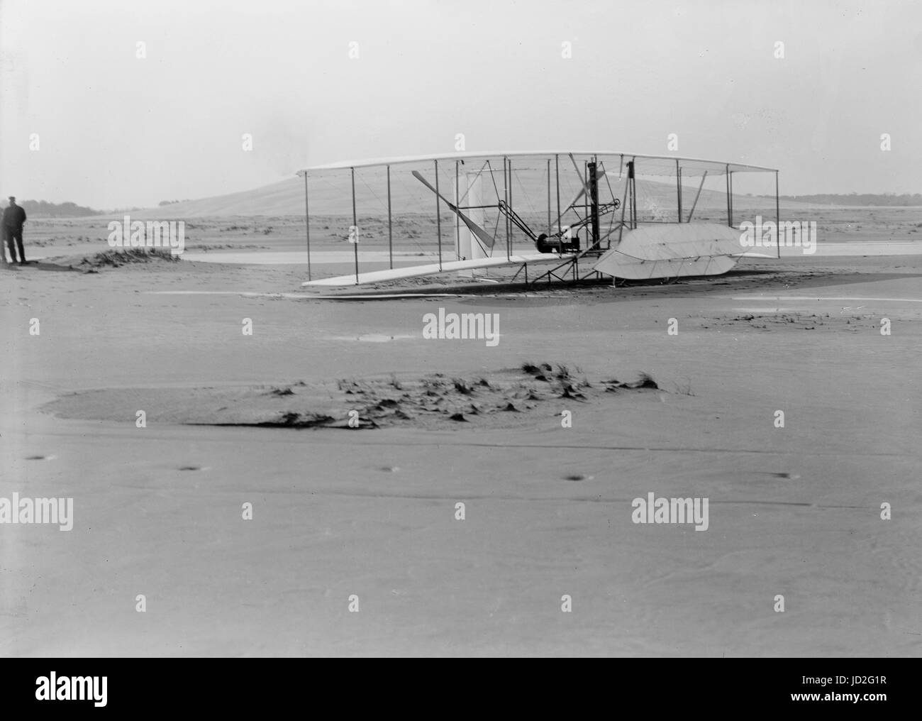 Close-up view of damaged 1903 machine, rudder frame broken in landing, on ground at end of last flight. - Stock Image