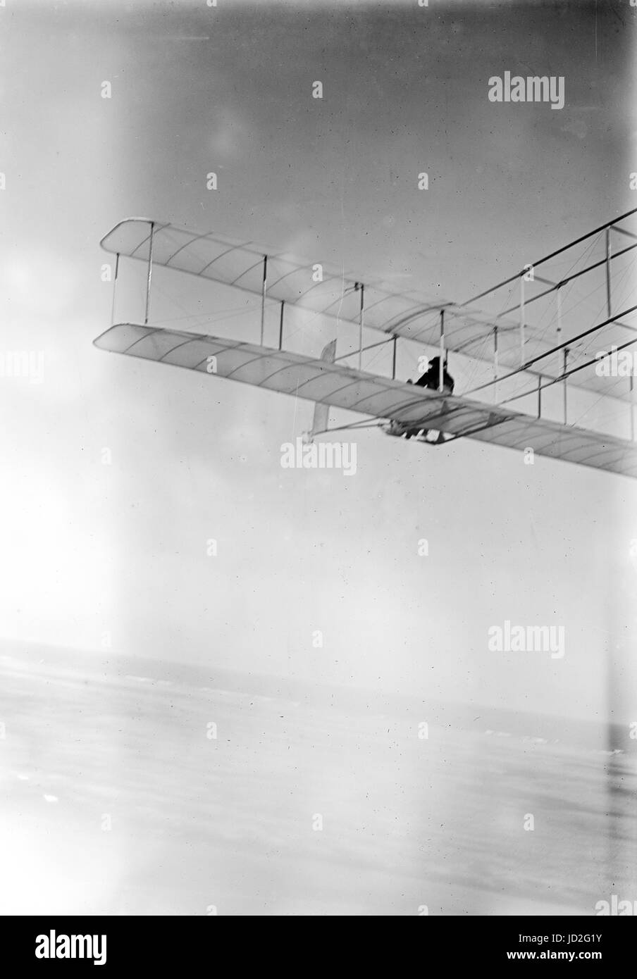 Three-quarter left rear view of glider in flight at Kitty Hawk, North Carolina. - Stock Image