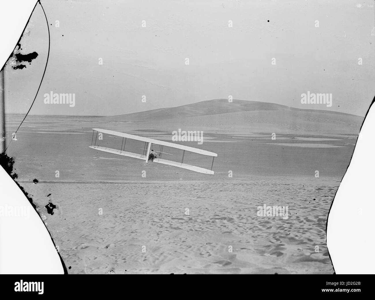 Rear view of Wilbur making a right turn in glide from No. 2 Hill, right wing tipped close to the ground. - Stock Image
