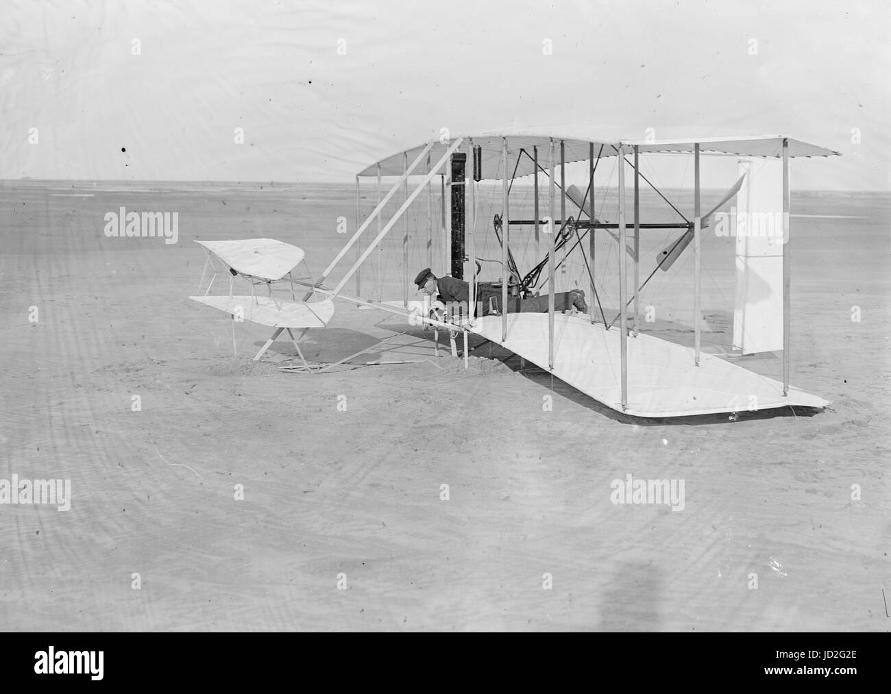 Wilbur in prone position in damaged machine on ground after unsuccessful trial of December 14, 1903; Kitty Hawk, - Stock Image