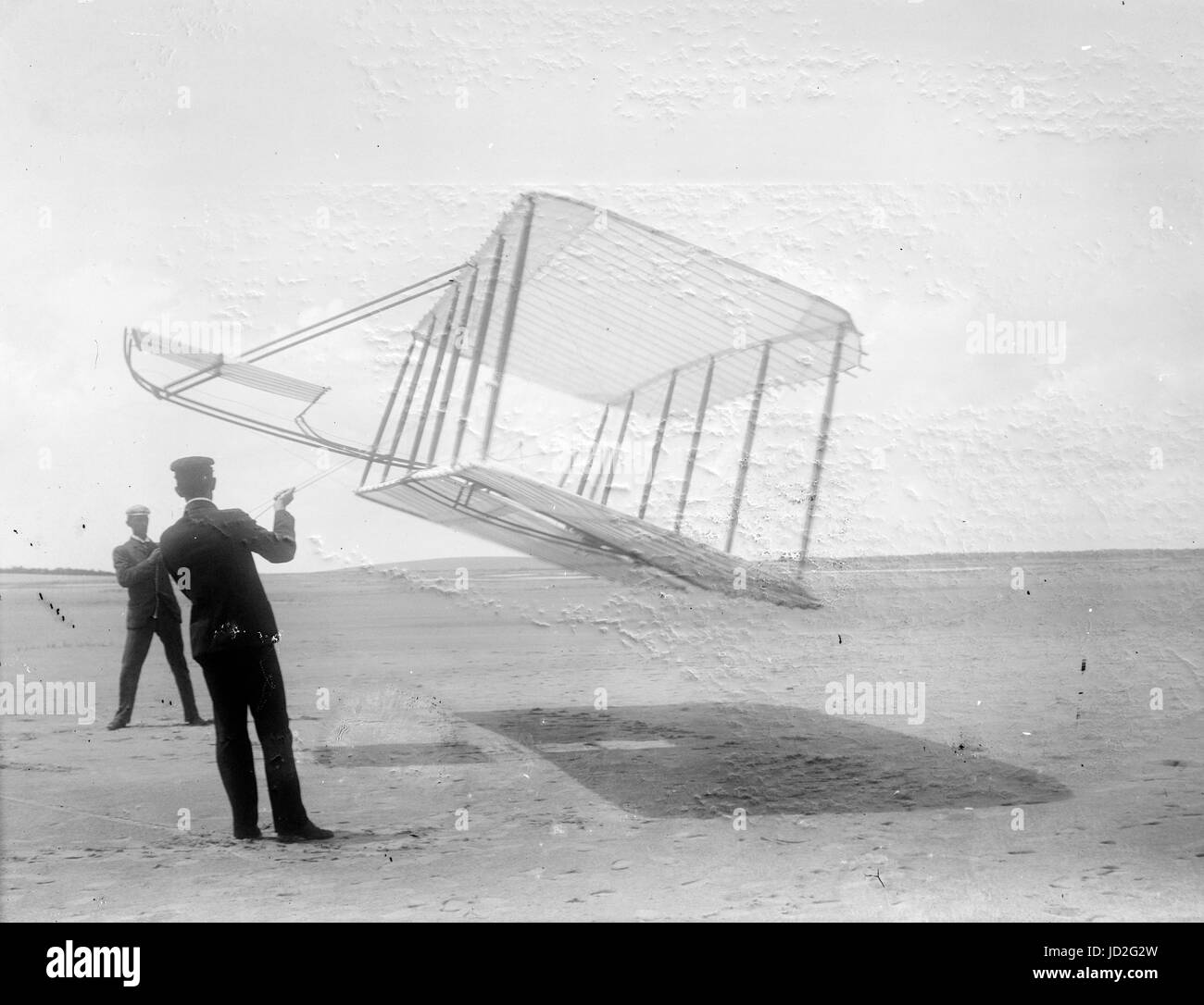 Side view of glider flying as a kite near the ground, Wilbur at left and Orville at right, glider turned forward - Stock Image