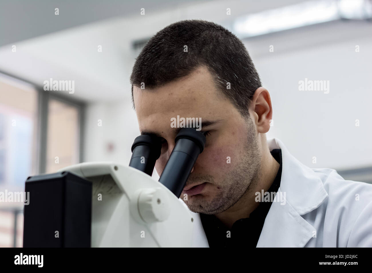 Female medical or scientific researcher man doctor looking through a microscope in a laboratory. Young scientist - Stock Image