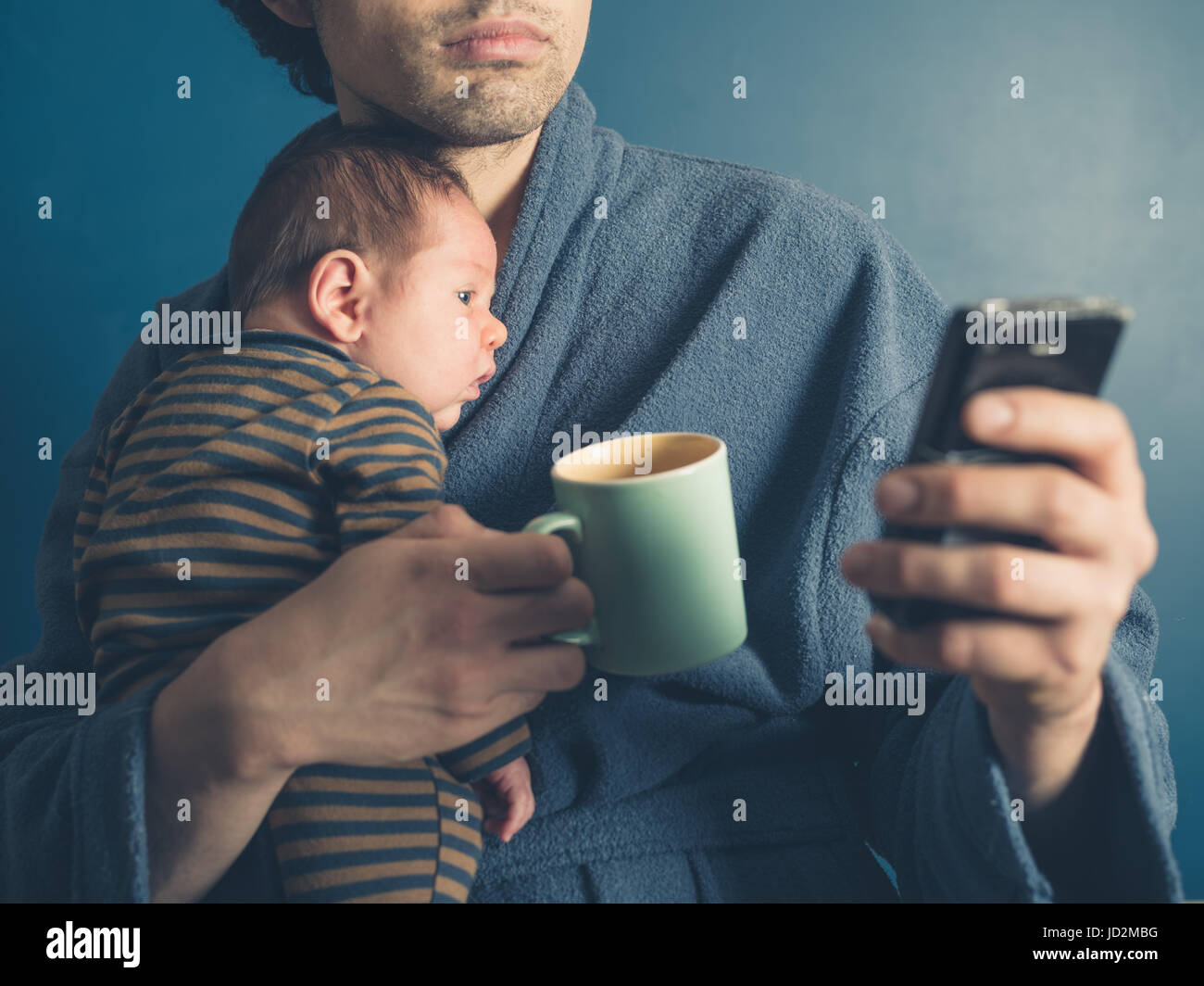 A young father in a bathrobe is using a smartphone whilst holding a mug and his baby son - Stock Image