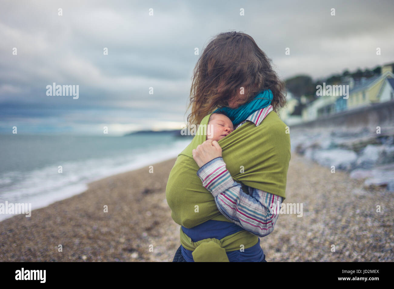 A young mother is by the sea with her baby wrappedd in a sling - Stock Image