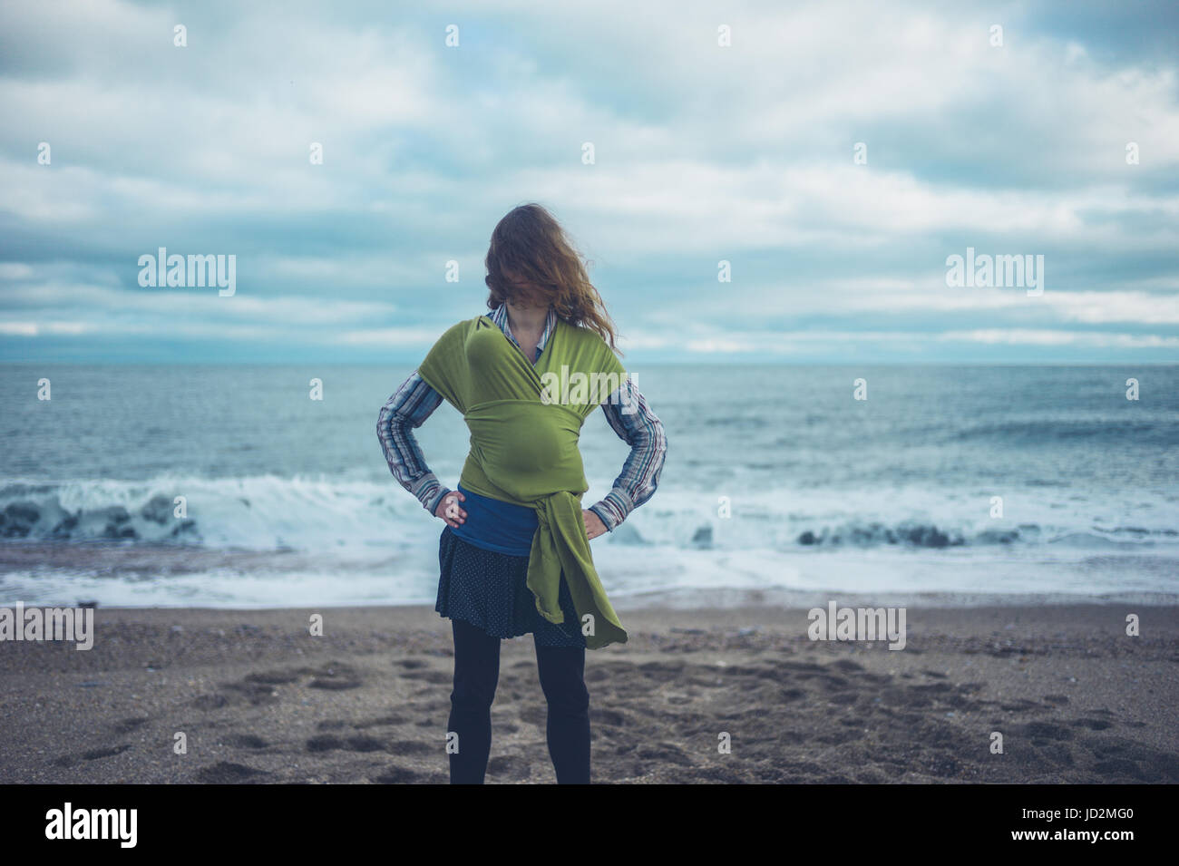 A young mother is standing on the beach with her baby wrapped in a sling - Stock Image