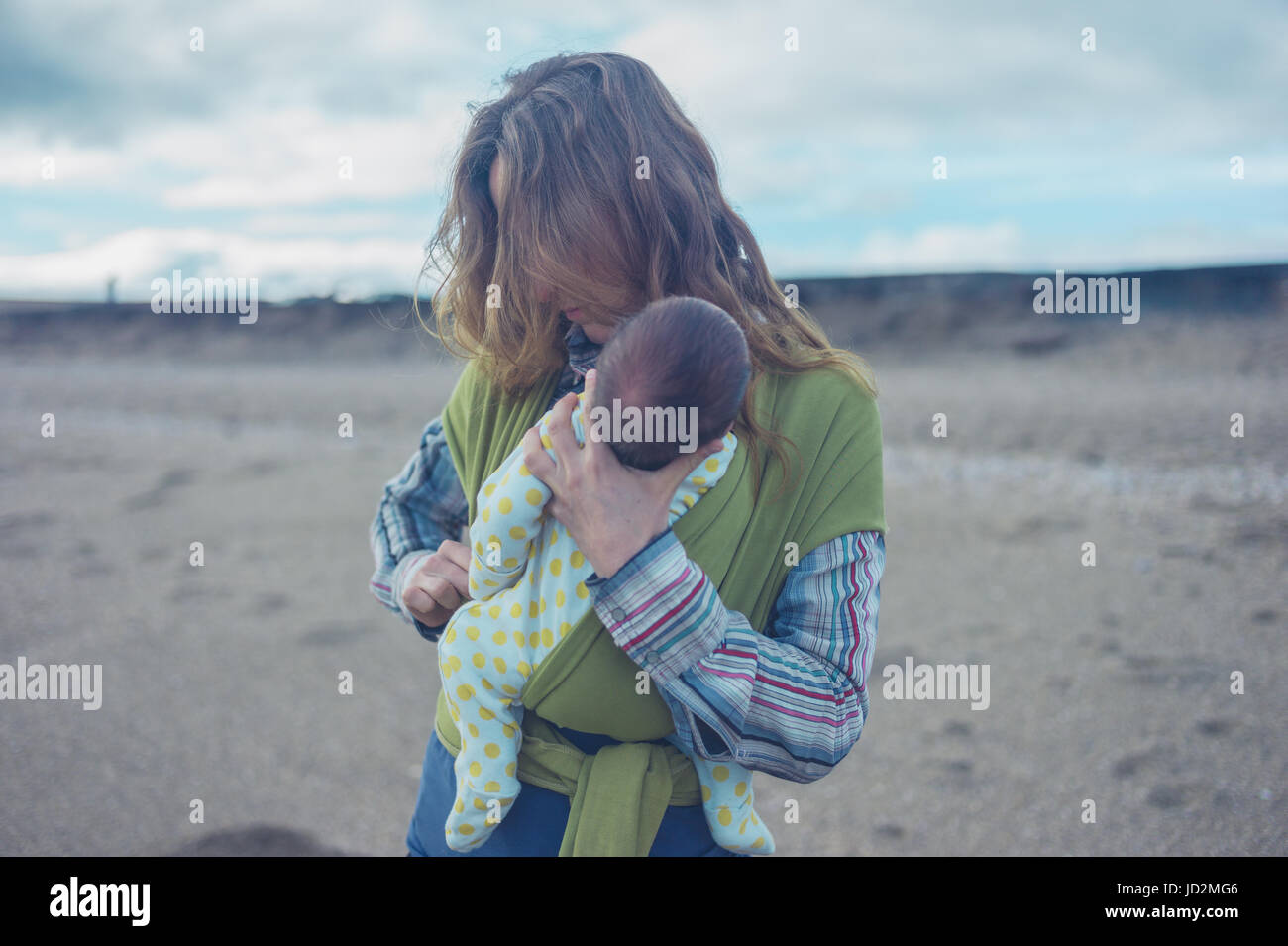 A young mother on the beach is putting her baby in a wrap - Stock Image