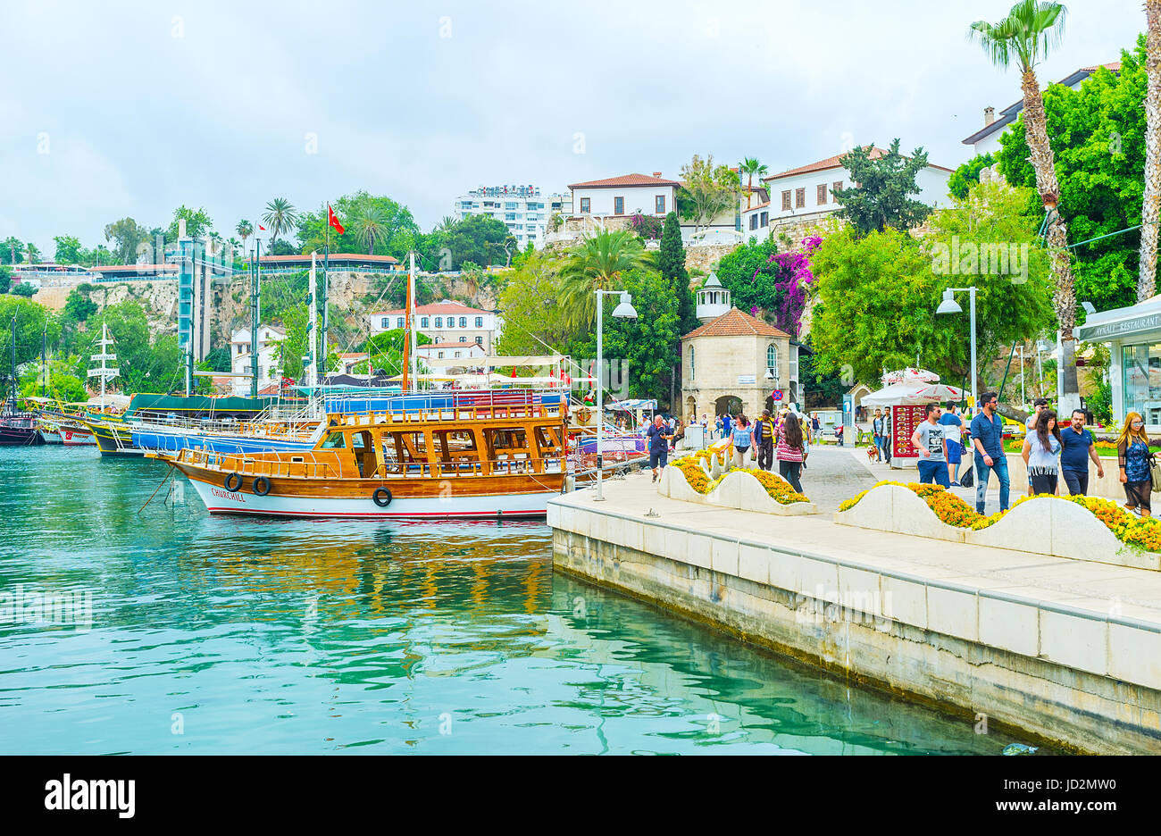 ANTALYA, TURKEY - MAY 6, 2017: The view of old marina with the preserved fortress walls, lush greenery, pleasure - Stock Image