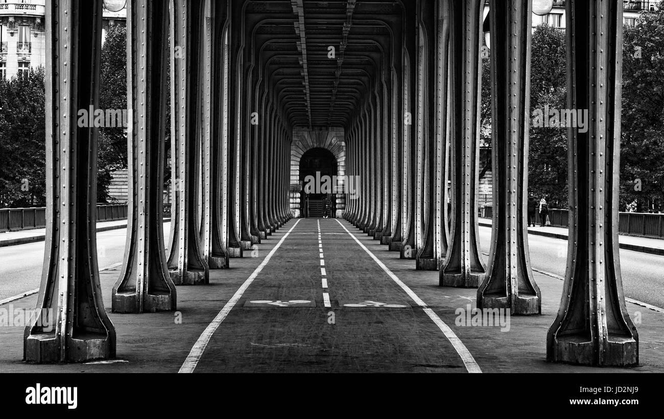Metal columns and abutments of '' Bir Hakeim '' bridge. People walks and make jogging under the - Stock Image
