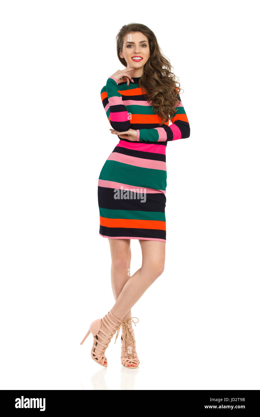 Beautiful young woman in colorful striped mini dress and high heels is standing with legs crossed, holding hand - Stock Image