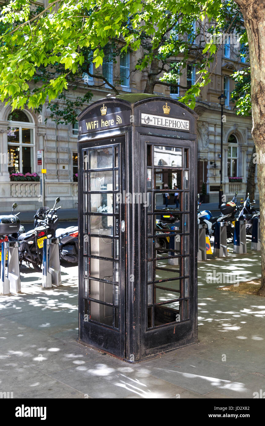 A black traditional phone booth in the Square Mile of London, UK - Stock Image