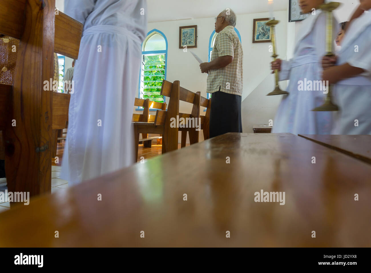 Low point of view indoors of Pacific Island man inside church holding hum sheet signs while procession enters Saint - Stock Image