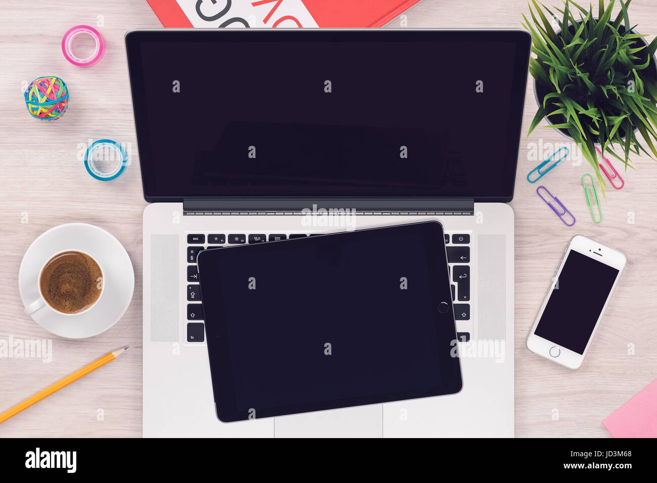 Top view flat lay workspace mockup with open laptop tablet pc and smartphone on office wooden desk - Stock Image