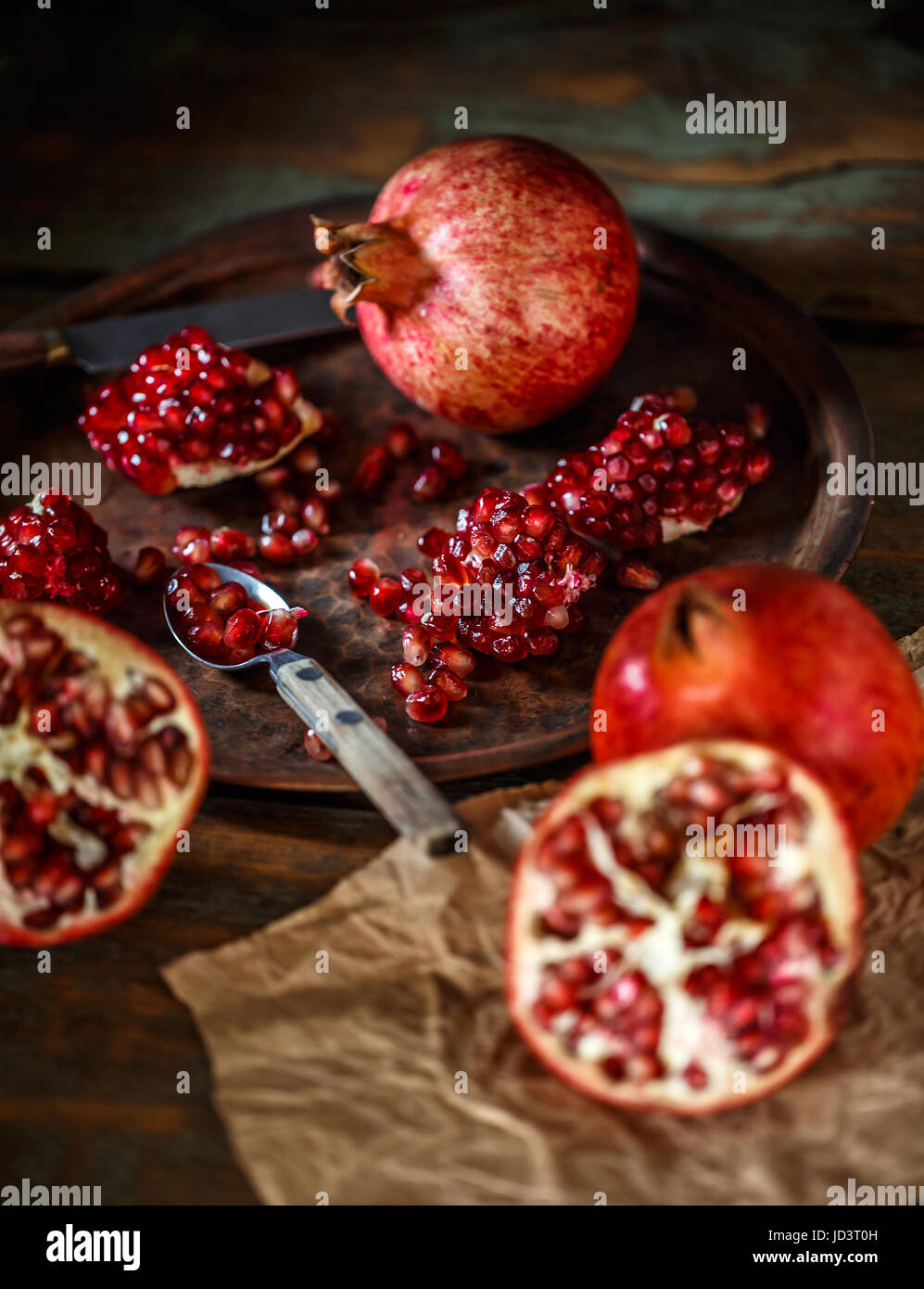 Red juicy pomegranate, whole and broken, on rustic background - Stock Image
