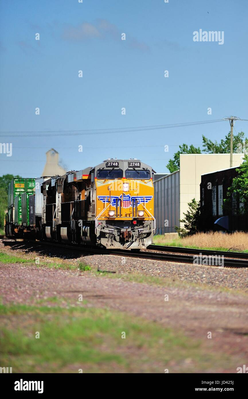 A westbound Union Pacific freight train with a heavy consist of freight as it roars through DeKalb, Illinois on - Stock Image
