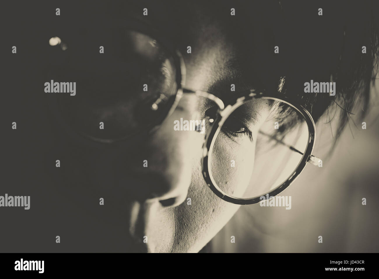 Headshot of women with round glasses looking downward concentrate on somethings in sepia color. - Stock Image