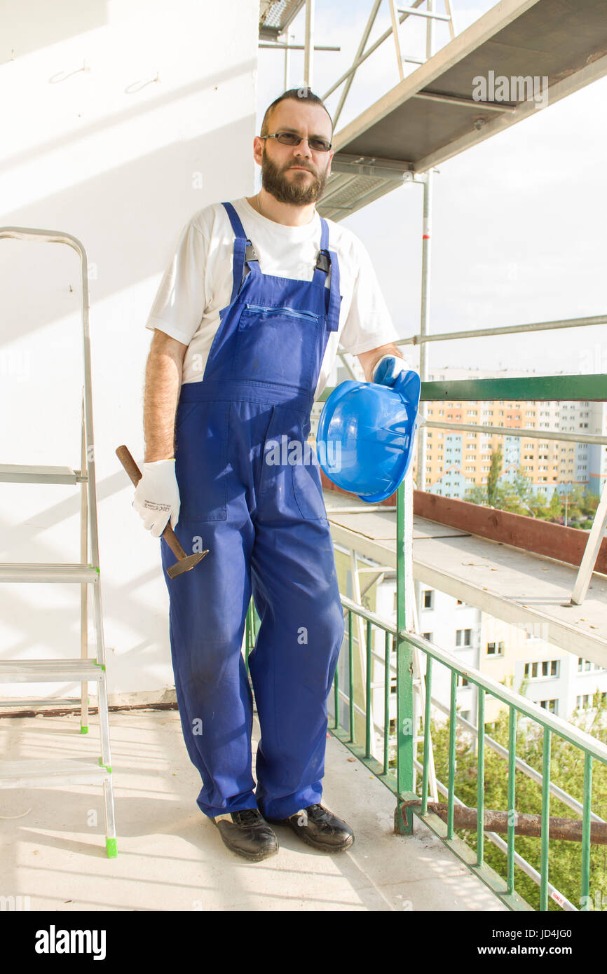 Construction worker in a work attire, protective gloves holds a helmet and a hammer. Work at high altitude. Scaffolding - Stock Image