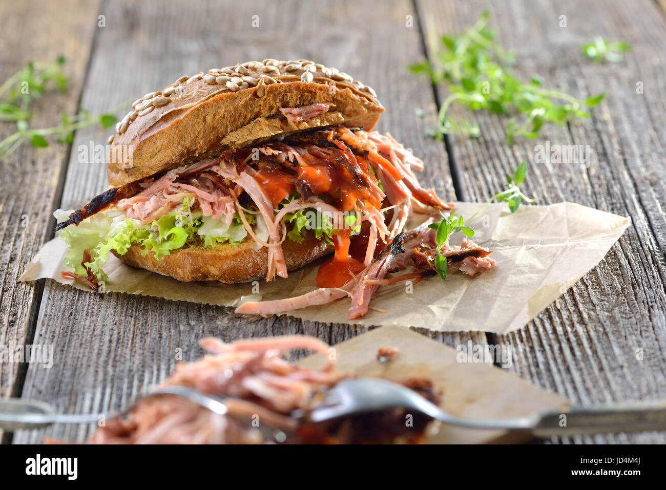 Street food: Barbecue pulled pork wholemeal sandwich with coleslaw, hot BBQ sauce served on brown wrapping paper - Stock Image
