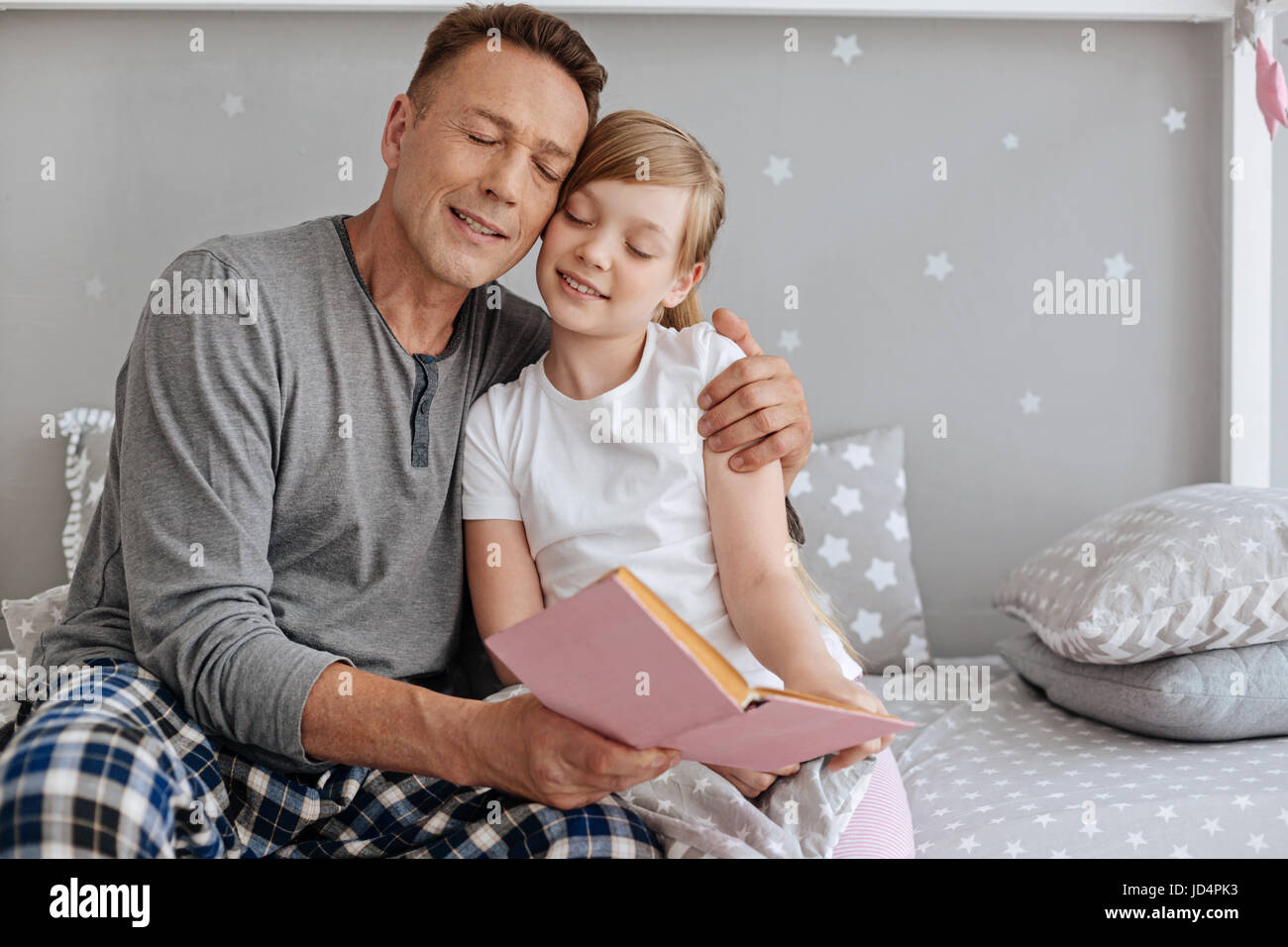 Affectionate charming father hugging his little girl - Stock Image