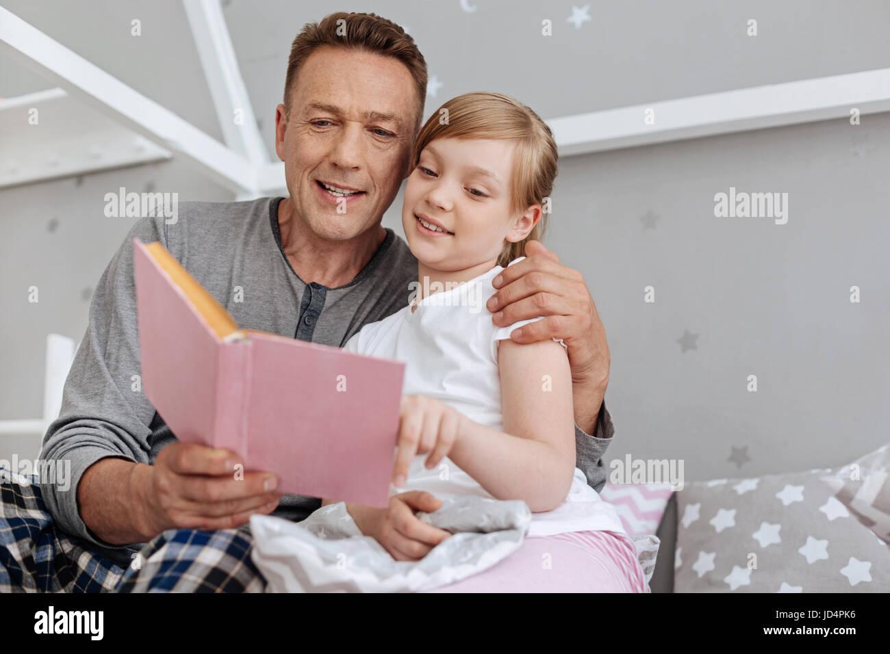 Nice loving man putting his child to sleep - Stock Image
